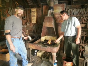 Jem Blueher and Andy Olds firing up the restored forge in the Blacksmith Shop.