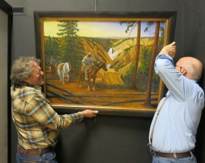 Bob Ebinger and Paul Shea hanging a Tom L. Roberts painting in art exhibit.