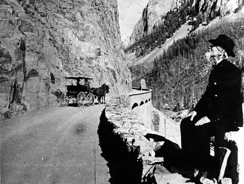 Man sitting alongside road at Golden Gate with horse-drawn wagon in background, Yellowstone National Park