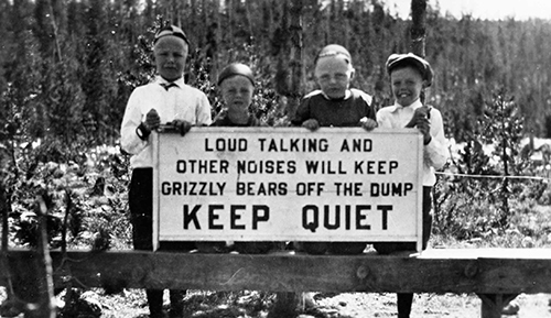 Four boys posing with sign to Keep Quiet because of bears feeding on platform