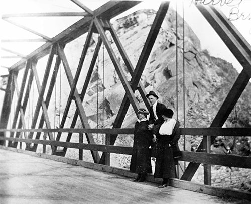 Three people posing on Harvat Bridge, east of Livingston