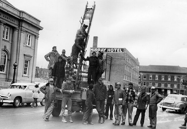 Men gather around truck and ladder, readying to put up holiday lights