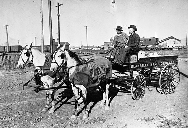 Two men driving a Blakeslee Brothers horsedrawn delivery wagon