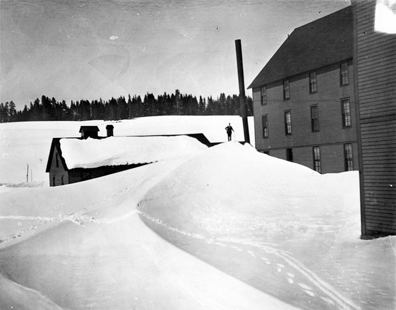 A skier stands atop a huge snowdrifts next to the second Canyon Hotel, Yellowstone National Park.