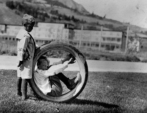 Two boys playing with a rubber tire, one inside, at Mammoth Hot Springs, Yellowstone National Parkis inside