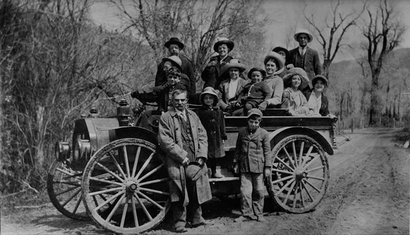 People piled into a car and standing in front of car.