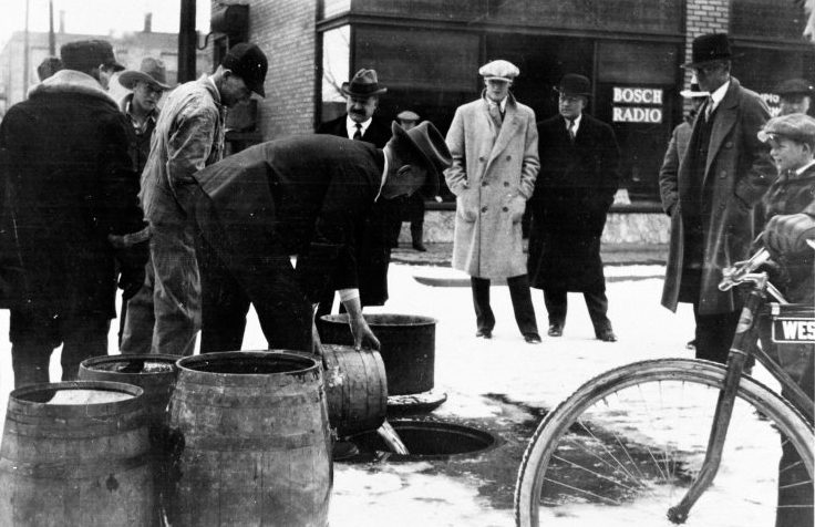 People gathered around confiscated liquor being poured down the drain.