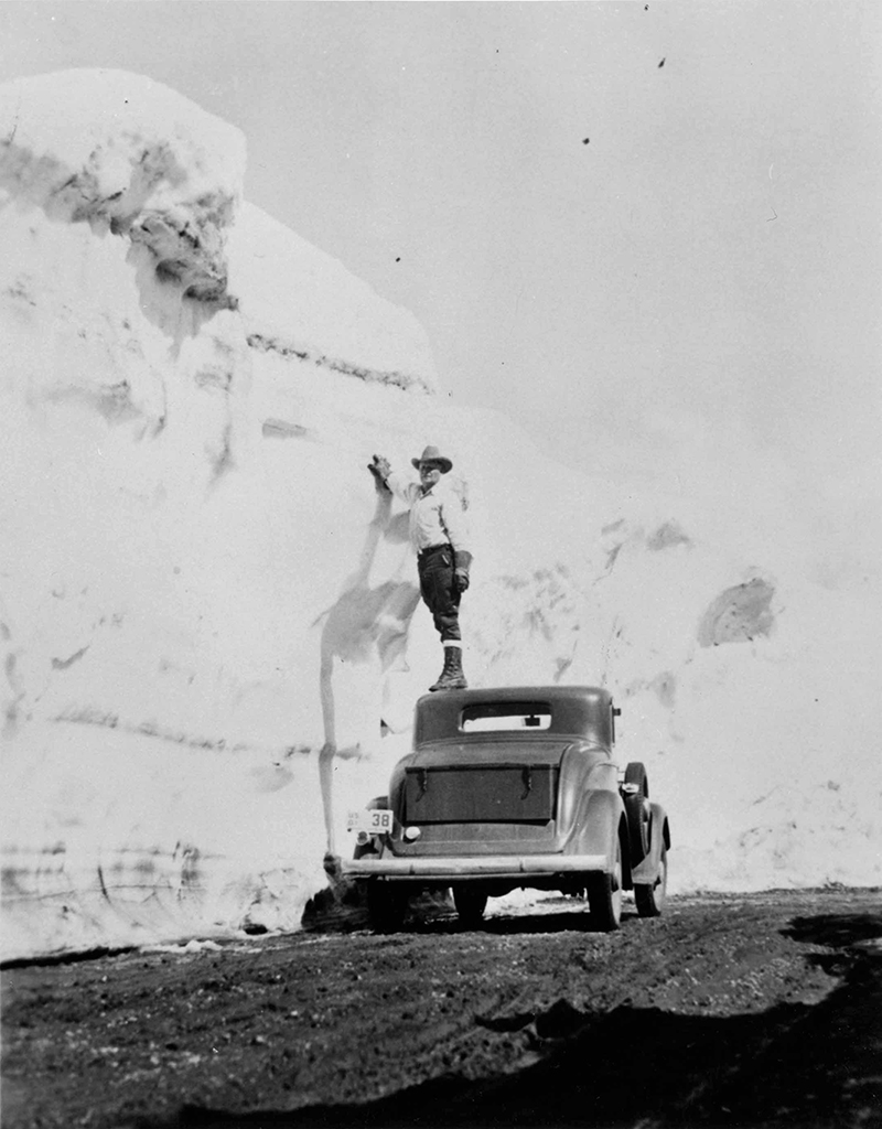 Man standing on car to give scale to 18' snowbank